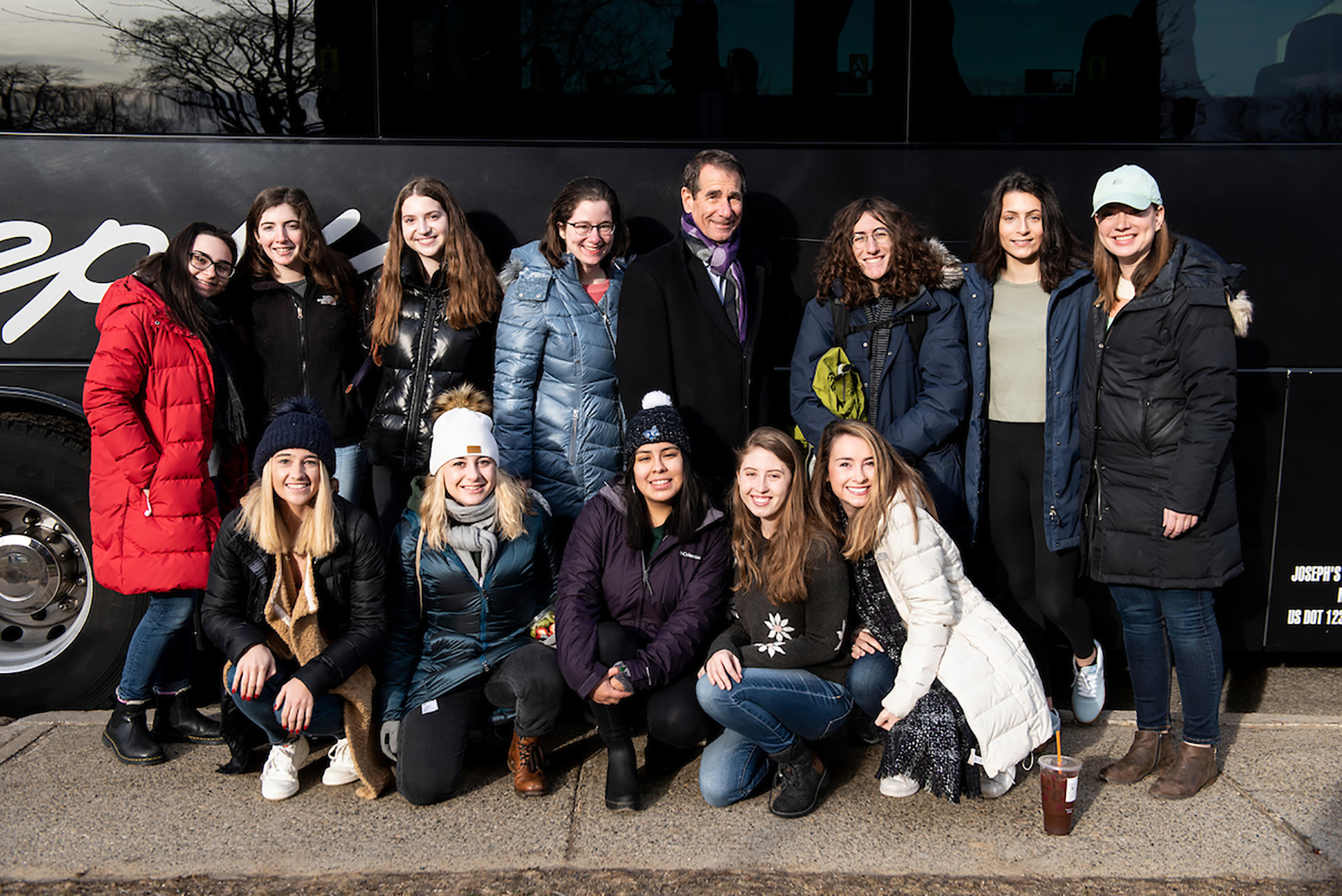 A group photo of 13 students and Tufts administrators