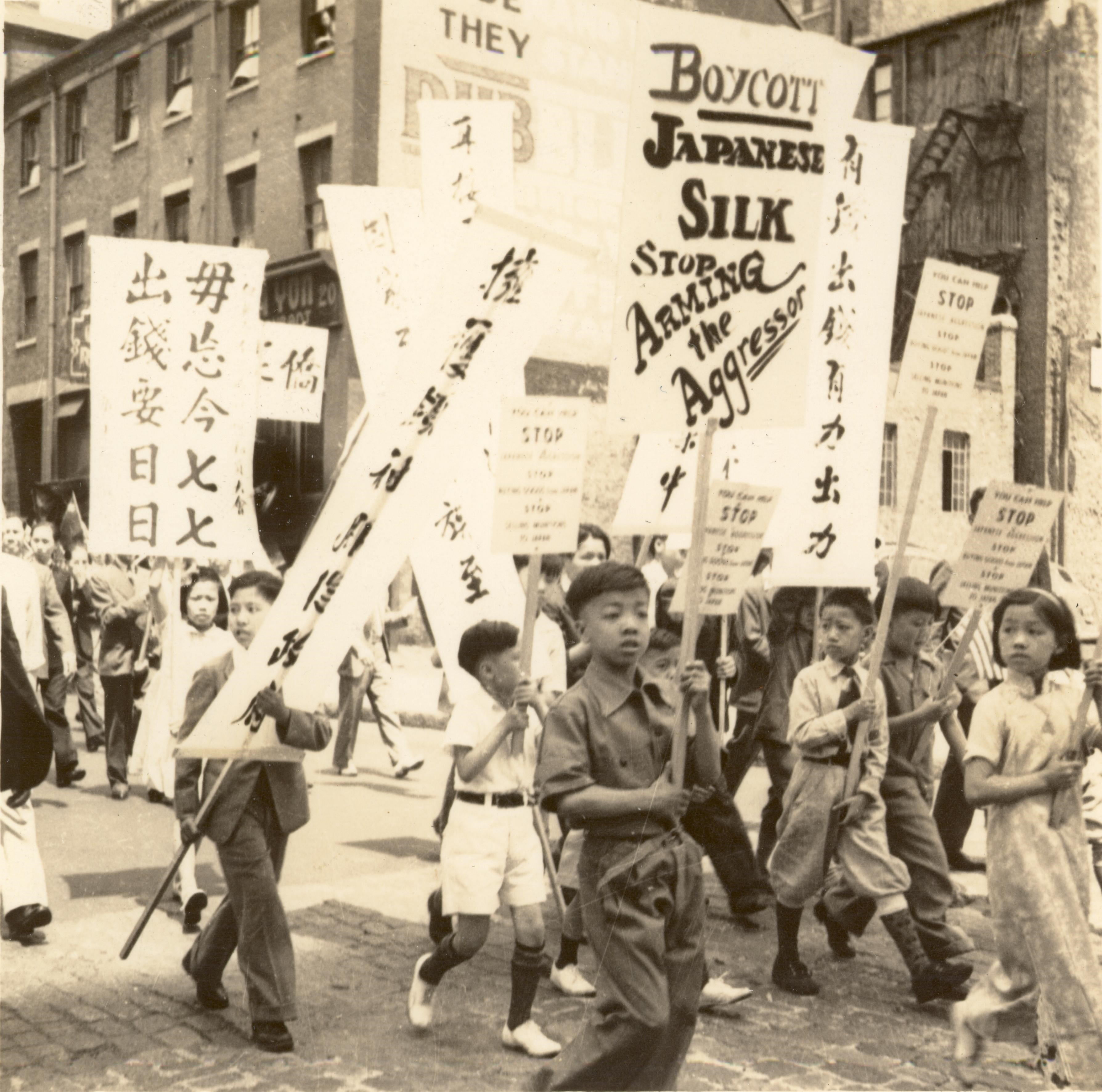 black and white image of young students holding signs in boycott of Japanese silk