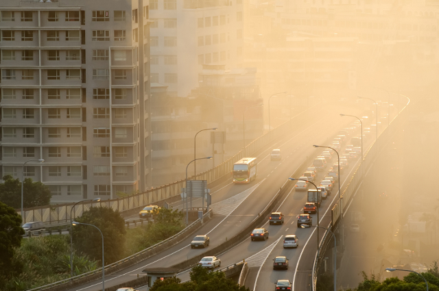 a highway going through a downtown area with heavy smog