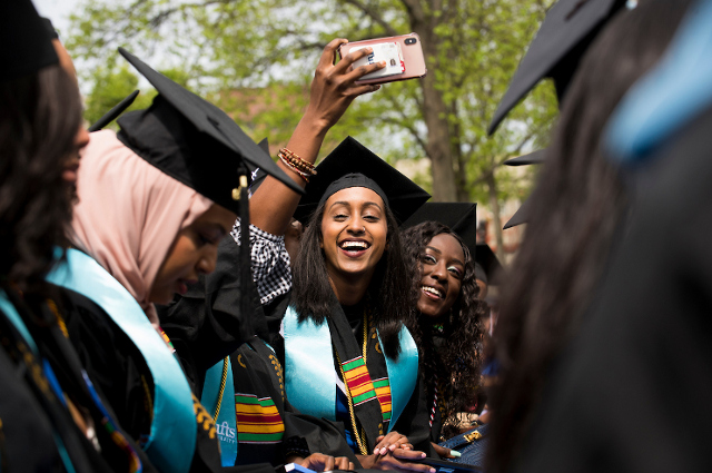 Happy graduates wave to each other at commencement