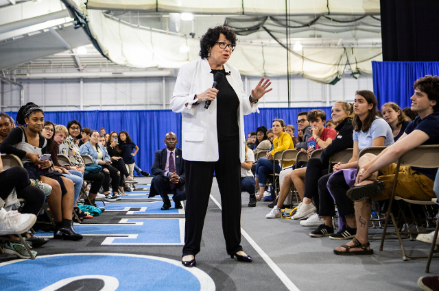 Sonia Sotomayor speaking into a microphone while standing in the aisle between large crowds of seated people. The Supreme Court justice told a large Tufts audience that we all need to speak up and be heard—and be willing to engage with others