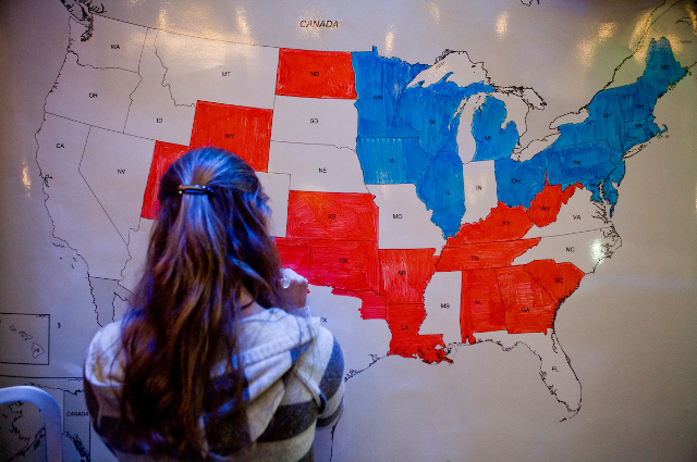A young woman looks at a national map divided between red and blue states. The new Tufts Campaign School will teach students how campaigns work