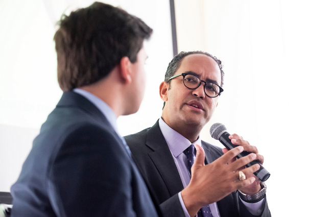 Man talking into a microphone, as another looks on. Will Hurd, a Republican Texas Congressman leaving the House of Representatives next year, tells a Tufts podcast that more unites us as a country than divides us.