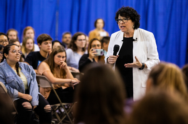 Woman with microphone walking amidst a seated crowd. Supreme Court justice Sonia Sotomayor talks agreeing to disagree, diversity of experience, and fallibility in a Tufts podcast