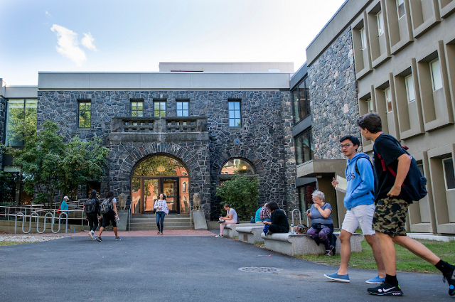 People milling about the front of a large building. A one-year renovation transforms Tufts landmark Barnum Hall into a place of new academic purpose and vitality.