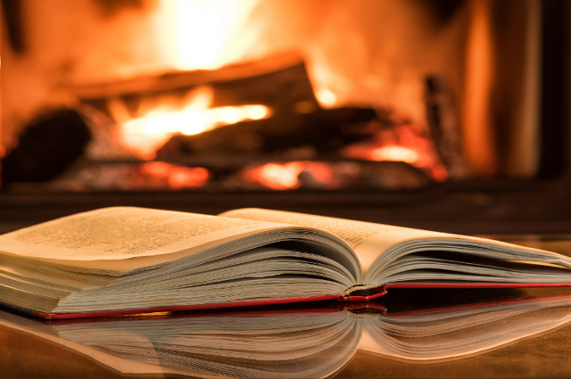 An open book in front of a fireplace. The Tufts community offers suggestions for books new and old.