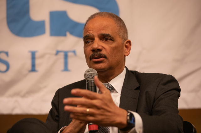 Eric Holder speaking into a microphone at Tufts University. In a Tell Me More podcast, the former U.S. Attorney General talks about being smart on crime, racism, and making life and death decisions