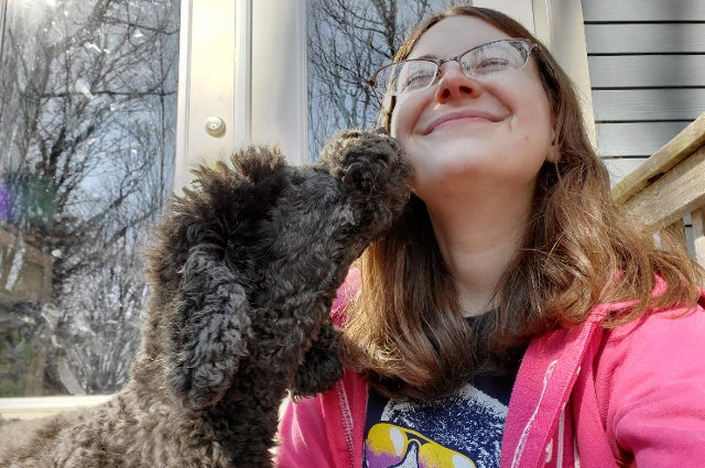 A woman being licked by her dog on her face. Pets can provide company and comfort in the face of social isolation and high anxiety
