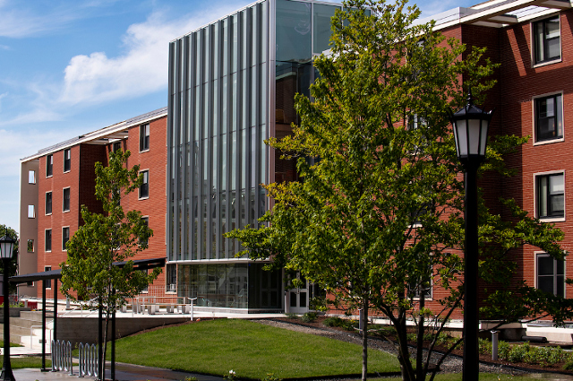 A brick and glass fronted building, one of the residence halls Tufts is offering to house medical personnel, first responders, and patients for local hospitals and host cities