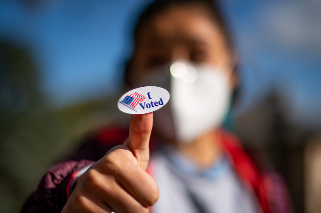 """Young woman with mask holding a """"I Voted"""" sticker. The presidential election shows the standoff in our national politics is growing more serious, says Tufts political scientist"""