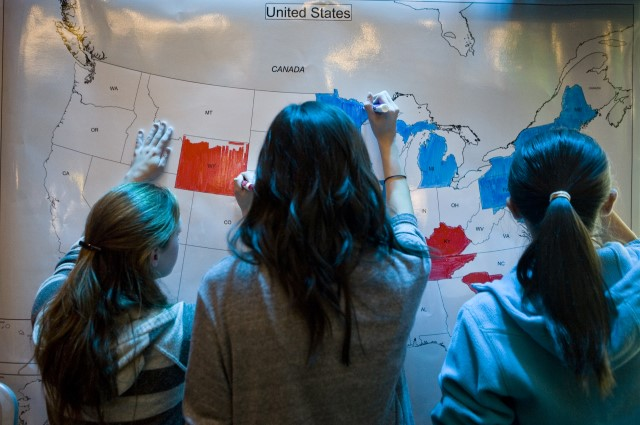 Students gathered in front of a wall map of the United States